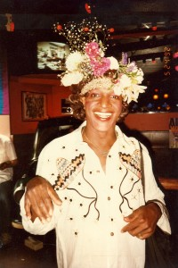 "A picture of a smiling, decadently beautiful flower arrangement hat wearing Marsha ""Pay It No Mind"" Johnson"