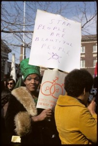 "Marsha P Johnson holding a sign that reads ""STAR PEOPLE ARE BEAUTIFUL PEOPLE"""