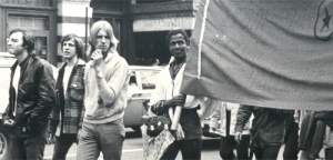 Marsha P Johnson holds part of a banner in a street action.